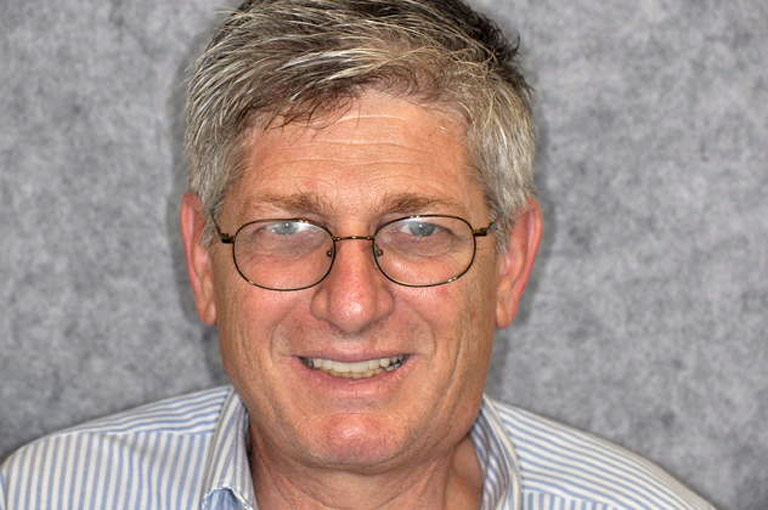 Headshot photo of gray-haired man with glasses smiling showing teeth after smile makeover
