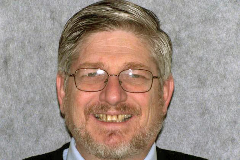 Headshot photo of gray-haired man with glasses smiling showing teeth before smile makeover