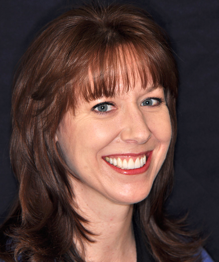 Headshot photo of brunette woman with bangs smiling showing smile makeover results from Weiss