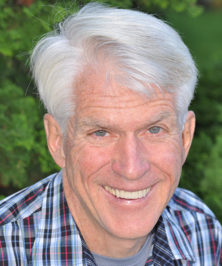 Headshot photo of older man in plaid shirt smiling showing smile makeover results from Weiss