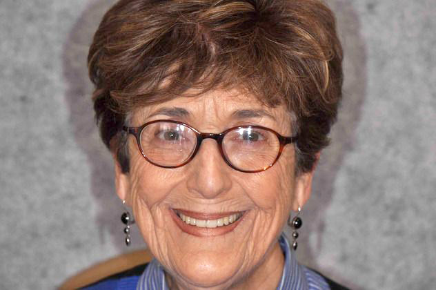 Headshot photo of older woman with glasses smiling showing teeth after smile makeover