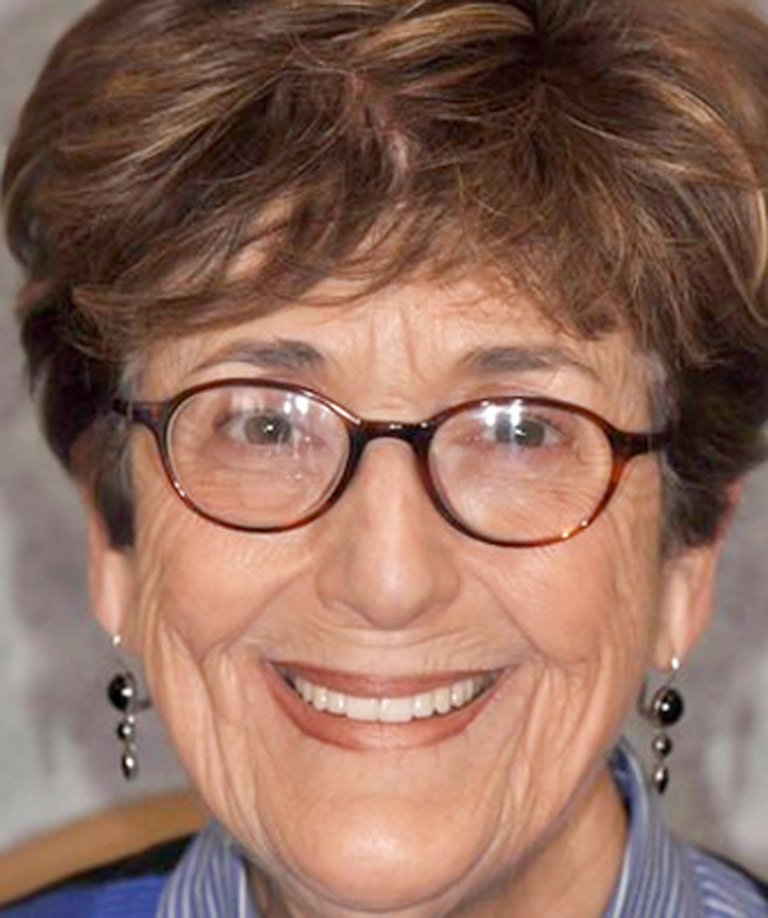 Headshot photo of older woman with glasses smiling showing smile makeover results from Weiss