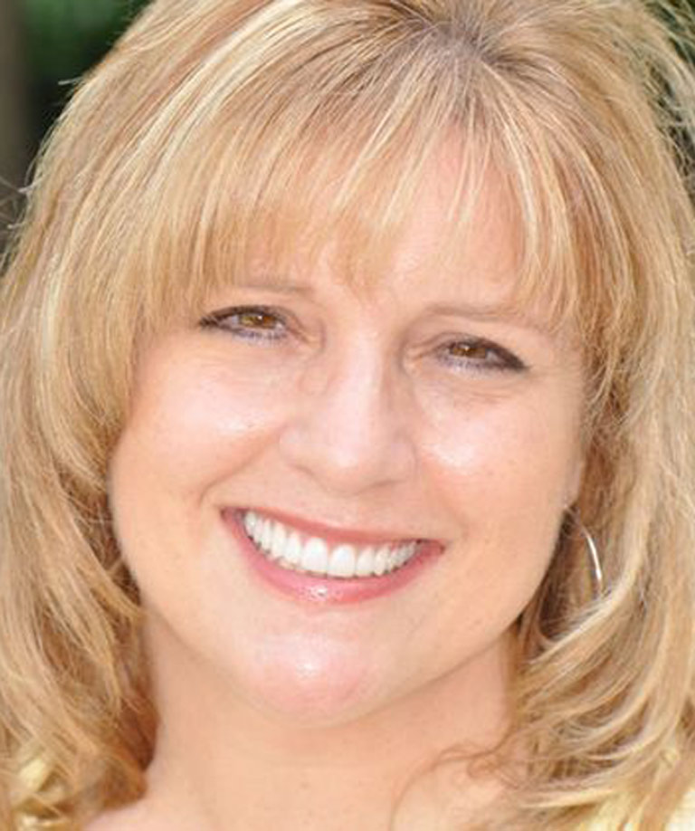 Headshot photo of middle-aged blonde woman smiling showing smile makeover results from Dr. Weiss