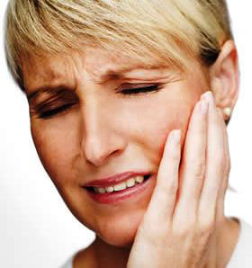 woman holding her her jaw in pain