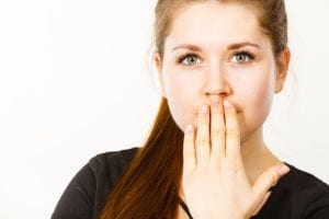 Woman covering her mouth with hand.